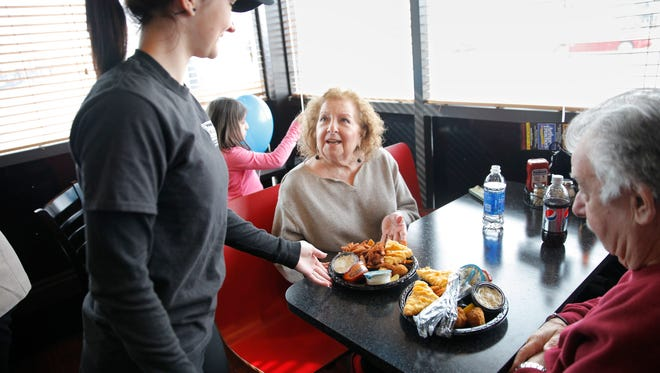 File Photo: Sandra Kosmider delivers Arthur Treacher's fish and chips dinners to Irondequoit residents Carmella and Louis Buchiere on Monday. The seafood restaurant opens in Webster Monday.