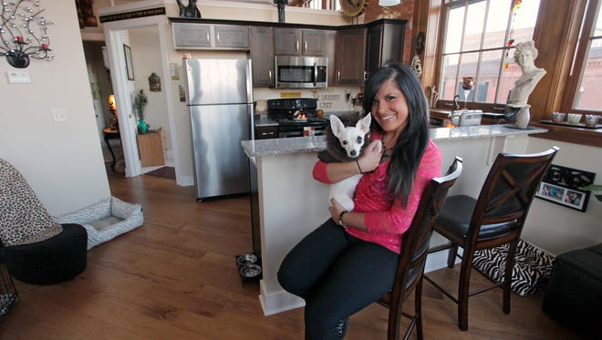 """Shumway, holding her  Chihuahua """"Gino,""""  loves her loft's open floor plan, but made sure it felt warm and inviting."""