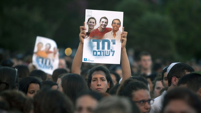 "Israelis hold a poster showing the three missing Israeli teens at a Tel Aviv rally under the slogan ""Bring Our Boys Home"" on June 29."