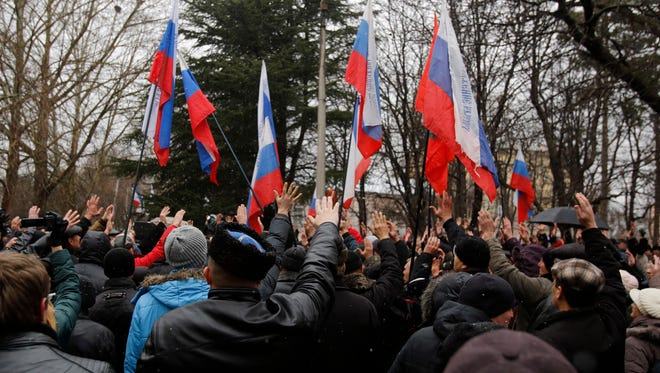 Pro-Russian demonstrators wave Russian and Crimea flags and shout slogans during a protest in front of a local government building in Simferopol, Crimea, Ukraine, on Feb. 27.