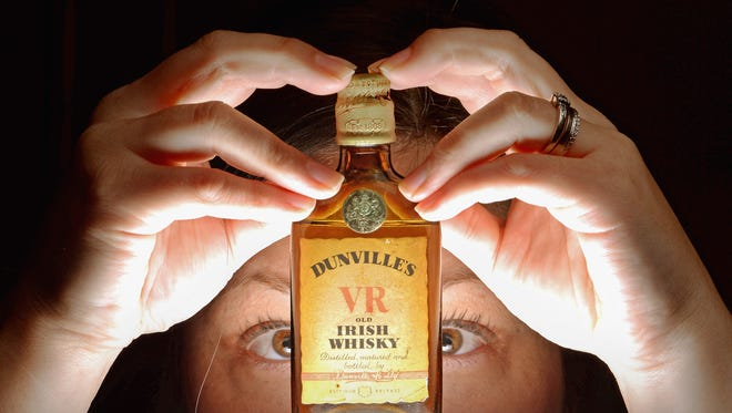 Whiskey specialist Lisa Mitchell at McTears auctioneers views lot 826 Dunville's V.R miniature old Irish Whiskey.