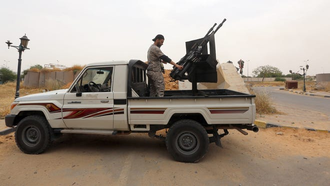 Former rebel fighters who are now integrated into the Libyan army and form the Diraa al-Gharbiya brigade are seen with their weapons guarding the western entrance of Tripoli on May 19.