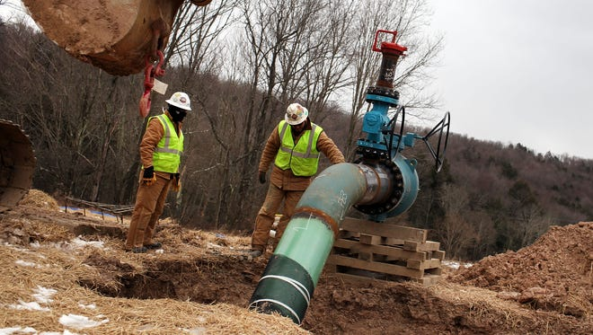 Cabot Oil and Gas employees work on a natural gas valve at a hydraulic fracturing site on Jan. 18, 2012, in South Montrose, Pa.