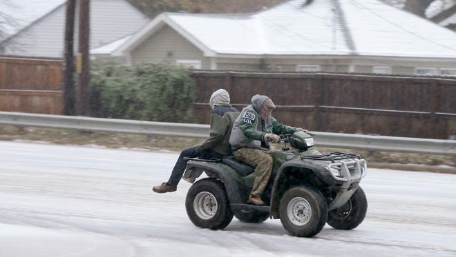 Two people ride an all-terrain vehicle on a sleet-covered street in Little Rock on Dec. 6, 2013. A new report documents the dangers of riding an ATV on public roads.
