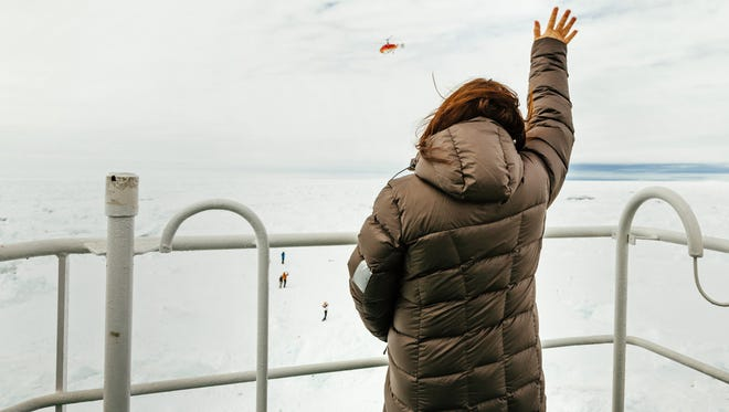"Passenger Nicole De Losa waves to a helicopter sent from the Chinese icebreaker ""Xue Long"" to assess ice conditions around the MV Akademik Shokalskiy on Dec. 29."