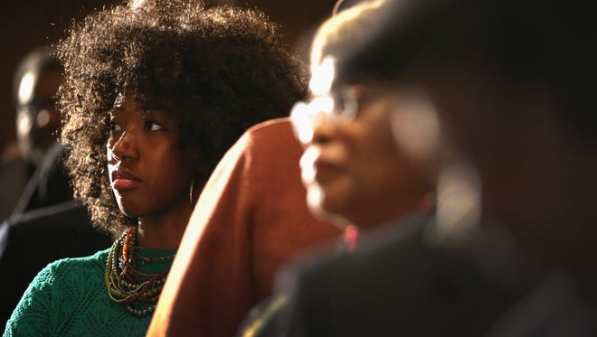Kelauni Cook waits in line to ask a question during a Dec. 19 town-hall-style meeting hosted by Al Sharpton to address gun violence in many of Chicago's African American neighborhoods. Of the nearly 1,000 murder victims in Chicago in the past two years, about 80% have been black men.