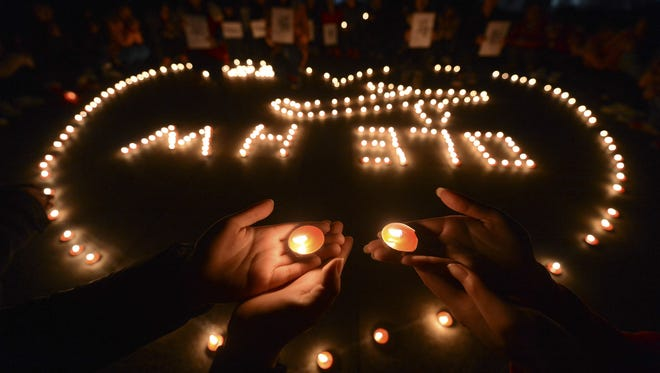 In this March 13, 2014 file photo, university students hold a candlelight vigil for passengers on the missing Malaysia Airlines Flight MH370 in Yangzhou, in eastern China's Jiangsu province. The disappearance of Malaysia Airlines Flight 370 has exposed wide gaps in how the world's airlines, and their regulators, operate. But experts warn this isn?t likely to be one of those defining moments that lead to fundamental changes.