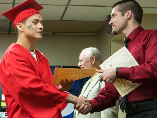 Christopher Long Solider shakes hands with one of his instructors, Nick Redmond during the graduation ceremony at the South Dakota Sate Penitentiary in Sioux Falls on Thursday, May 10, 2018.