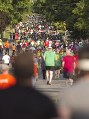 A throng of runners head down Clinton Street in Howell