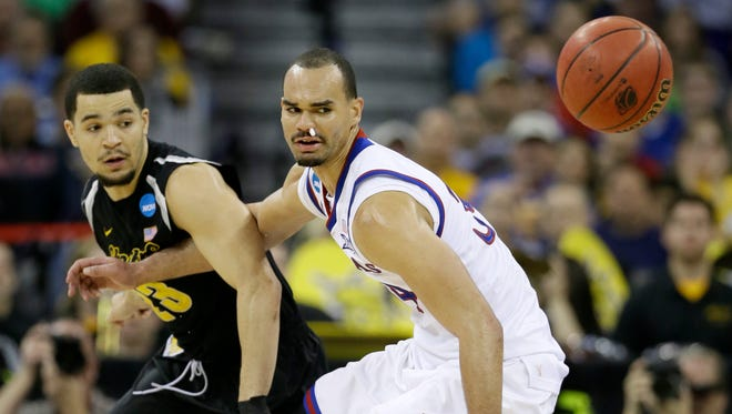 Wichita State guard Fred VanVleet, left, fights for the ball with Kansas forward Perry Ellis during the first half of an NCAA college basketball tournament round of 32 game on Sunday in Omaha, Neb. No. 7 seed Wichita State beat second-seeded Kansas, 78-65.