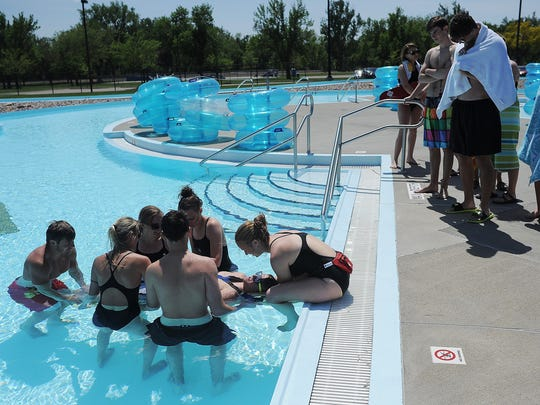 """Lifeguards work through a training exercise where a 10-year-old, played by lifeguard Kade Walker, has a head and possible neck in jury, in the """"Lazy River"""" at Drake Springs Family Aquatic Center on Thursday, May 21, 2015, in Sioux Falls."""