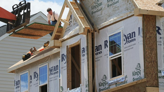 Builders work on the roof of a home under construction at a housing plan in Jackson Township, Butler County, Pa. On Friday, June 16, 2017, the Commerce Department reports on U.S. home construction in May.