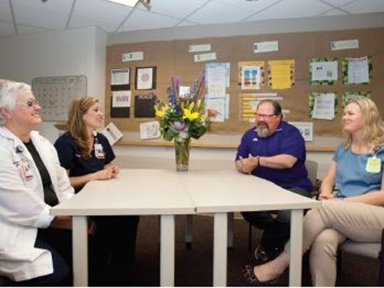 From Left, Jane Arndt, clinical nurse specialist for Wound Ostomy Continence Care, PVH surgical unit Nurse Coordinator Casey Newth, former patient Kurt Kues and Bridget Froelich, PVH surgical unit nurse and educator, take a few minutes to reminisce about Kues' several-month stay in PVH's surgical unit 10 years ago. Every year since he was in the hospital, Kues has brought the unit's nurses flowers for Nurses' Week as a thank you.