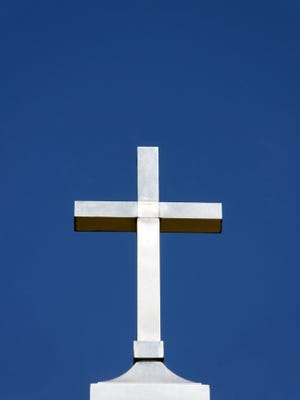 Metal Cross Against a Clear Blue Sky