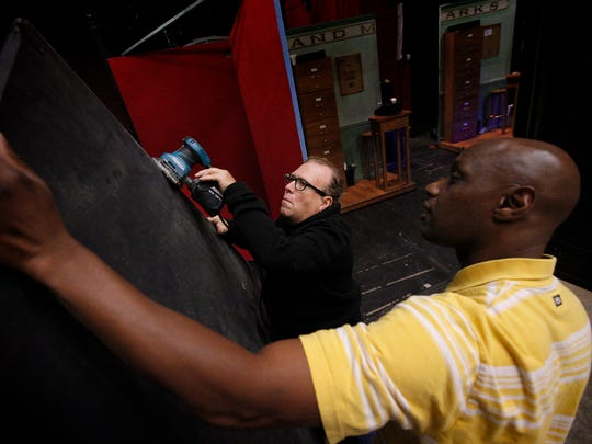 Head props Dale Stanton sands a prop for the set of The Producers while stage hand Clarence Mason holds the board. The duo, both of Elmira, are employed through the local union, ISTCE 289.