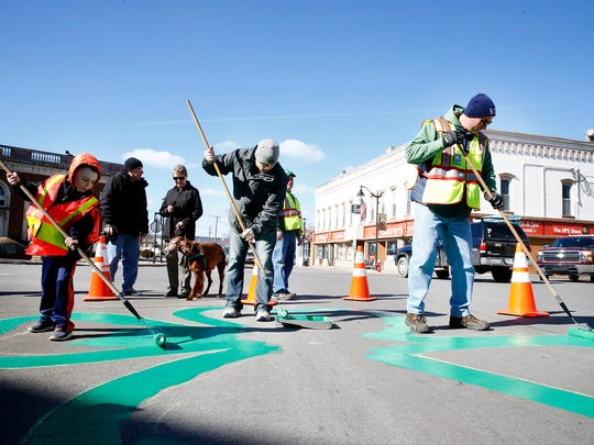 Brogan Sullivan, 6, left, and Horseheads firefighter Kevin Sullivan, right, paint a large, green shamrock in Hanover Square Sunday as volunteer Chris Bell, center, puts paint on his roller.