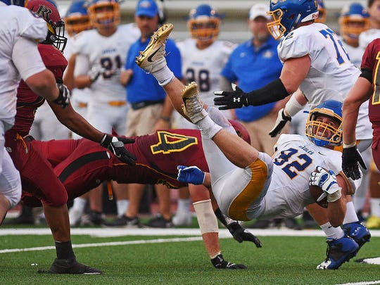 Aberdeen Central's Collin Stoebner (82) is brought down by Roosevelt's Gustaf Radel (64) during a game Friday, Aug. 26, 2016, at Howard Wood Field in Sioux Falls.