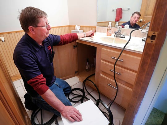 Water flows out a bathroom faucet after Greg Miller with Anderson Plumbing thaws frozen pipes with an electrical device Wednesday, December 27, 2017, in the home of Grant Gudeman in the Hawk's Nest subdivision in West Lafayette.