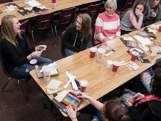 "Faith Butler, left, laughs as she reads a quote that was put in her ""I Am"" cup by Kaitlin Lansing during their Hurt to Hope group session Thursday afternoon at the Pike County YMCA."