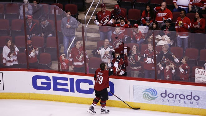 Arizona Coyotes' Shane Doan tosses a puck to a fan during pregame warm-ups against Detroit Red Wings on Jan. 14, 2016 in Glendale, Ariz.
