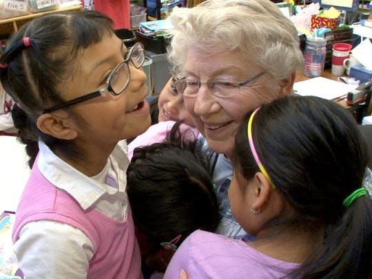 Marshall W. Errickson Elementary School volunteer Virginia McCall gets hugs from kindergarten students at the Freehold Township school Wednesday, April 5, 2017.  She is one of the volunteers from the Applewood retirement community serving as teaching aides for school.