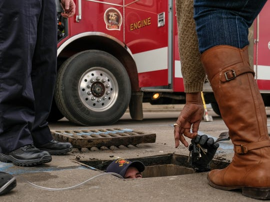 Waterford Fire Department probationary engineer Andrew Bartal hands Cheryl Randolph of Pontiac her keys after retrieving them from a drain Randolph dropped them in at a parking lot in Waterford on Friday February 16, 2018.