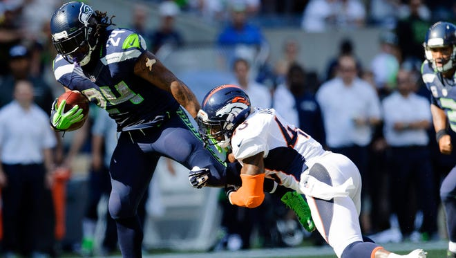 Seattle Seahawks running back Marshawn Lynch, left, fights for yards while Denver Broncos strong safety T.J. Ward tries to make a tackle in the second half at CenturyLink Field on Sunday.