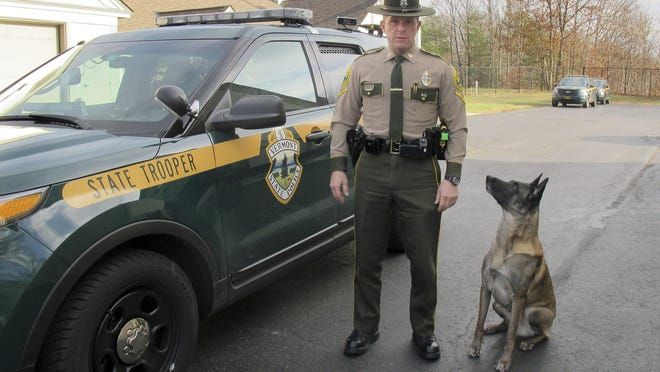 Vermont State Police Trooper Richard Slusser, who regularly stops speeders traveling faster than 100 miles per hour, poses with his dog Drager beside his cruiser outside the state police barracks in Royalton. Slusser catches most of the excessive speeders in the southbound lane of Interstate 89 near the Sharon/Royalton town line.
