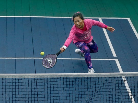 Rachel Bigby of Fairport picks up a low ball during a paddle tennis tournament at the Tennis Club of Rochester.
