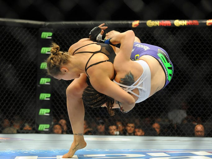 Jul 5, 2014; Las Vegas, NV, USA; Ronda Rousey (red gloves) takes down Alexis Davis (blue gloves) during the first round of a bantamweight fight at Mandalay Bay Events Center. Mandatory Credit: Stephen R. Sylvanie-USA TODAY Sports
