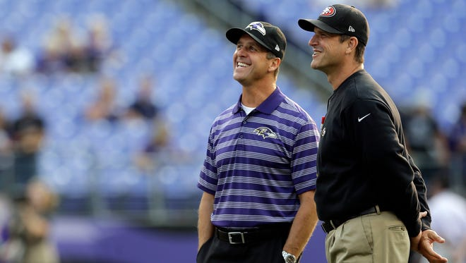 Baltimore Ravens head coach John Harbaugh, left, and San Francisco 49ers head coach Jim Harbaugh chat before an NFL preseason football game, Thursday, Aug. 7, 2014, in Baltimore. (AP Photo/Patrick Semansky)