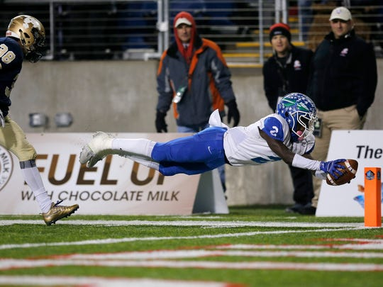 Winton Woods Warriors specialist Rae'Quan Prince (2) dives into the end zone as he runs back a kickoff for a touchdown in the second quarter of the OHSAA Div. II State Championship game between Archbishop Hoban and Winton Woods at Tom Benson Hall of Fame Stadium in Canton, Ohio, on Thursday, Nov. 30, 2017. At halftime, Hoban led 42-14.