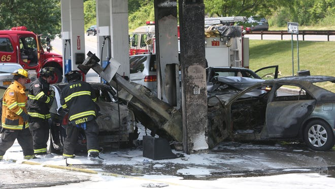 White Plains firefighters work at the scene of an accident and fire in the Mobil station on the Hutchinson River Parkway in White Plains June 3, 2014.