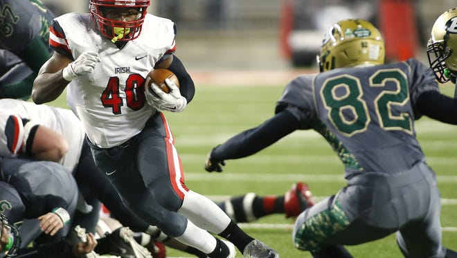 Toledo Central Catholic's Michael Warren (40) tries to elude Athens' Trey Keiffer (82) in the first half of a high school Div III championship football game, Thursday, Dec. 4, 2014, in Columbus, Ohio. (AP Photo/Mike Munden)