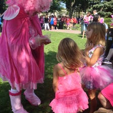 Cathy Burns of Livonia hands out stickers to Kenzie and Kylie Hatfield of Columbus, Ohio, who made the trek to support their mom, who was walking.