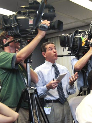 WTHR-13 reporter Jeremy Brilliant (center) asks a questions during a news conference at the City-County Building in 2010.
