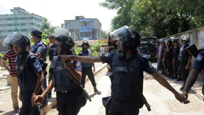 Bangladesh police stand guard at the scene of an operation to storm a militant hideout in Narayanganj, Bangladesh. Police stormed a militant hideout outside Dhaka August 27, shooting dead three militants, including the suspected mastermind of a horrific cafe attack last month.