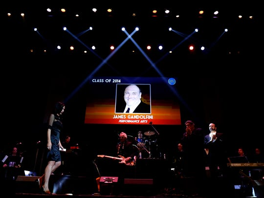 Deborah Lin, left, walks on stage as a photograph of her late husband, James Gandolfini, is displayed moments before she accepted Gandolfini's induction into the New Jersey Hall of Fame, Thursday, Nov. 13, 2014, in Asbury Park, N.J. Gandolfini, who played the lead role in the cable series The Sopranos, was inducted into the hall of fame during the event.