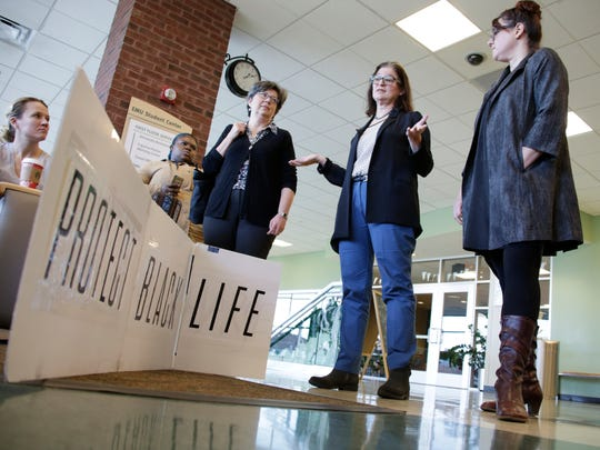 EMU professor of english literature Carla Harryman, center, describes a meeting with administration regarding four students who had been expelled for protesting racist graffiti. They are at Eastern Michigan University in Yspilanti  at the campus student center on Friday, November 18, 2016.