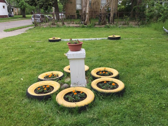 Patricia Kobylski has decorated two vacant lots near her home on Detroit's east side with planters made from used tires. Kobylski said on May 23, 2017, that keeping her neighborhood neat is important and is why she lobbied city officials to remove the debris from an illegal demolition near her home.