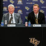 New UCF NCAA college football coach Scott Frost, center, is flanked by school president John C. Hitt, left, and athletic director Danny White during a news conference to introduce the new coach in Orlando, Fla., Wednesday, Dec. 2, 2015.