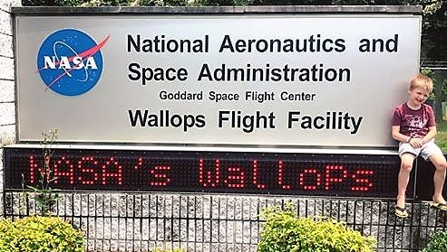 Jaxsen Palmer sits on the NASA Wallops Flight Facility sign during a recent vacation to Chincoteague, Virginia provided by the Casey Cares Foundation.