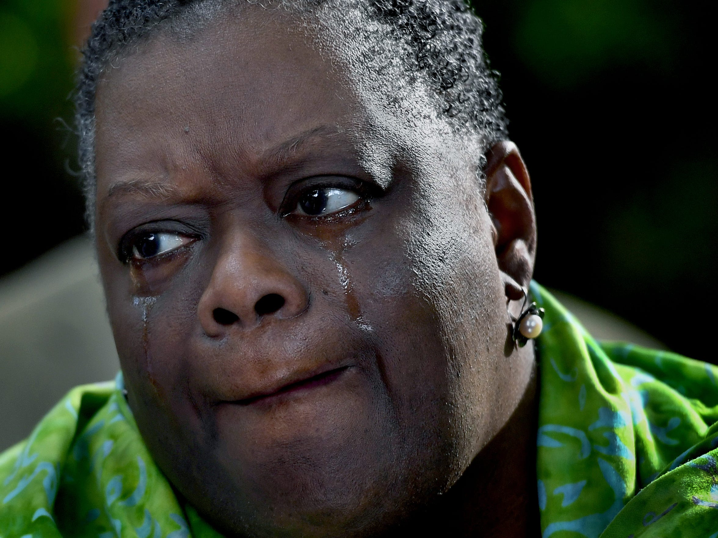 Brenda Brown-Grooms, a local pastor, cries during the