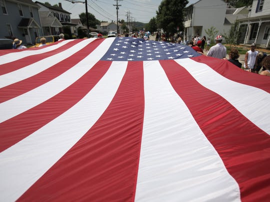 Members of the Harrison Historical Society carry a