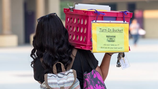 A teacher carries materials to her classroom on the first day of school at Alpine Vista Elementary in Tulare on Wednesday, August 8, 2018.