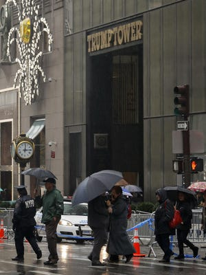 Pedestrians walk near Trump Tower in New York on Wednesday. President- elect Donald Trump said he is leaving his businesses, and it appears that his three eldest children will take over the operations.