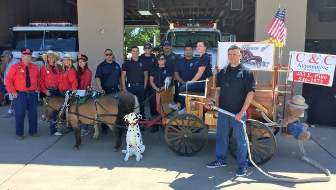Bob Bruce, far left, posed with members of the Deming Fire Department on Saturday after the PNM Tournament of Ducks parade. DFD Chief Raul Mercado is standing in the foreground with a fire hose.