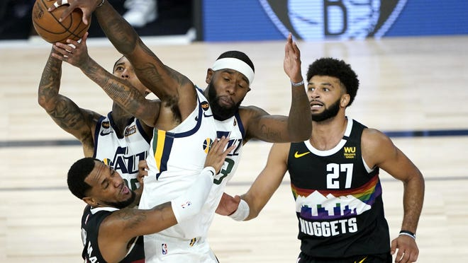 Utah Jazz's Jordan Clarkson, back, competes for a rebound with teammate Royce O'Neale, right, and Denver Nuggets' Monte Morris, left, during overtime Monday in Lake Buena Vista, Fla.