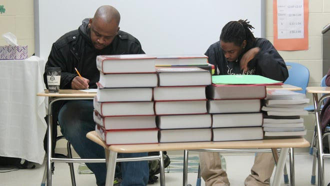 Writer Kiese Laymon, left, and Tate High School student Marquice Williams, right, work on a writing exercise Friday at the school.