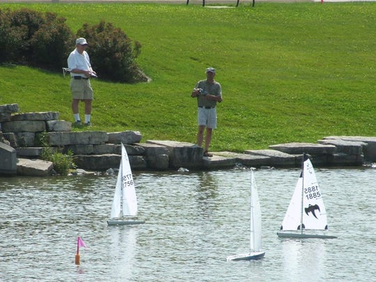 It takes concentration to maneuver radio-controlled sailboats from shore.  In this photo, two racers tack upwind toward a buoy the third boat has already rounded.